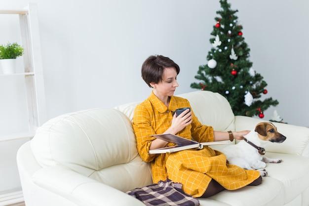 Szczęśliwa młoda kobieta czytanie książki w domu.