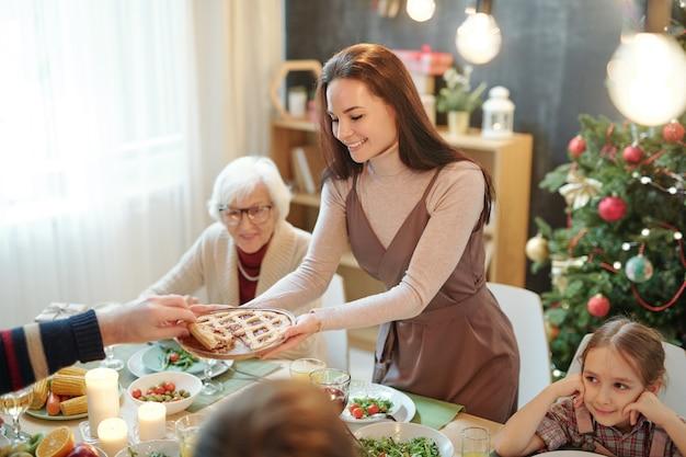 Szczęśliwa młoda kobieta, dając ojcu domowe ciasto przy świątecznym stole podczas rodzinnej kolacji w domu