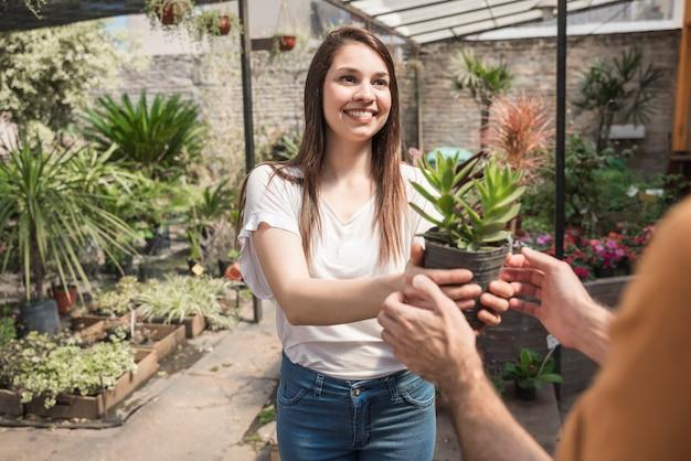 Szczęśliwa młoda kobieta daje doniczkowej roślinie jej klient w szklarni
