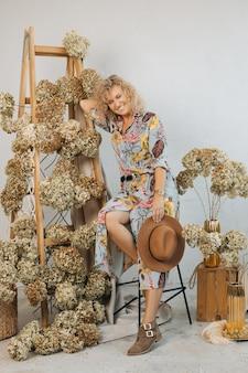 Szczęśliwa młoda kobieta dekoratorka z kapeluszem, stojąca uśmiechnięta i świecąca ze szczęścia. koncepcja udanej pracy i robienia tego, co kochasz. naturalny wystrój w studio. zdjęcie pełnej długości