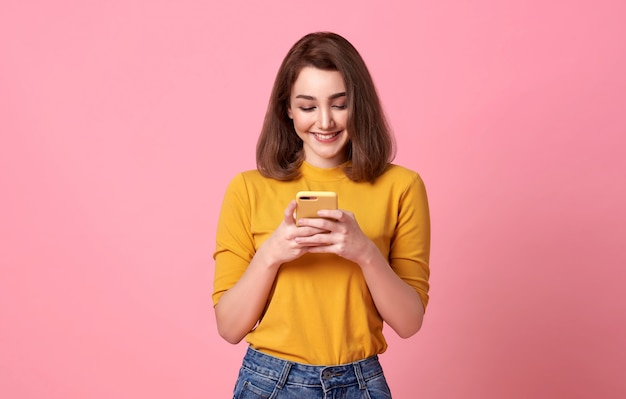 Szczęśliwa młoda kobieta dobry patrząc za pomocą telefonu komórkowego na białym tle nad różową przestrzenią.