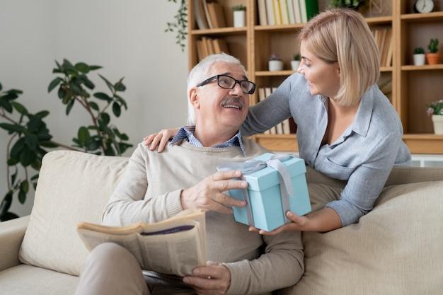 Szczęśliwa młoda kobieta dorywczo dając jej ojca w wieku zapakowane urodziny lub prezent gwiazdkowy w pudełku, patrząc na niego z uśmiechem