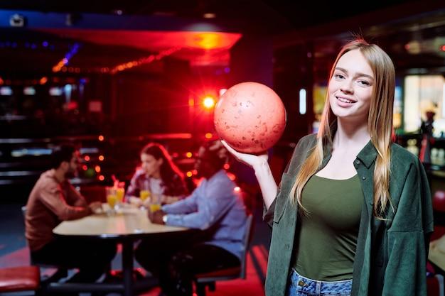 Szczęśliwa młoda kobieta dorywczo z długimi blond włosami trzymając kulę do kręgli podczas gry w centrum rozrywki z przyjaciółmi na ścianie