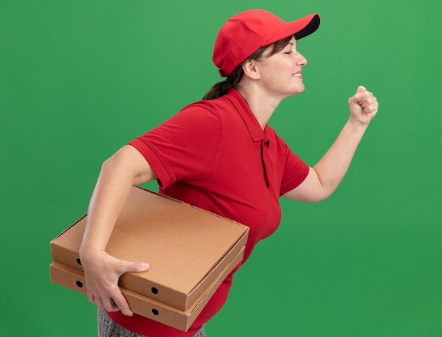 Szczęśliwa młoda kobieta dostawy w czerwonym mundurze i czapce pędzi do dostarczania pudełek po pizzy dla klienta na zielonej ścianie