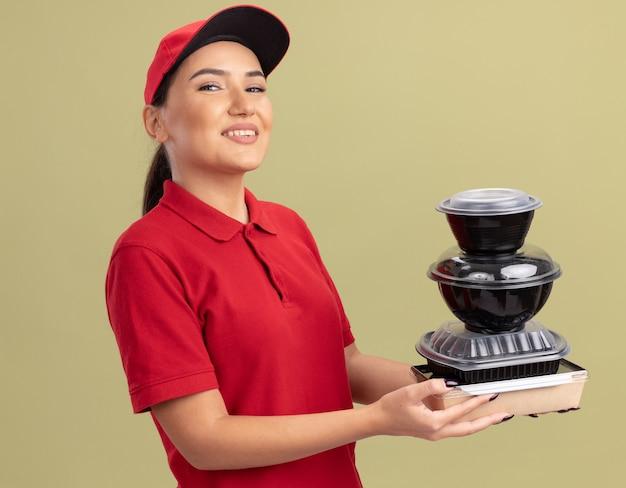 Szczęśliwa młoda kobieta dostawy w czerwonym mundurze i czapce trzyma stos opakowań żywności patrząc na przód uśmiechnięty radośnie stojący nad zieloną ścianą