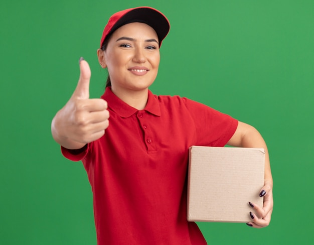 Szczęśliwa młoda kobieta dostawy w czerwonym mundurze i czapce, trzymając karton patrząc na przód, uśmiechając się radośnie pokazując kciuki do góry stojąc nad zieloną ścianą