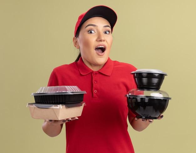 Szczęśliwa młoda kobieta dostawy w czerwonym mundurze i czapce, trzymając opakowania żywności, patrząc na przód, szczęśliwa i zaskoczona stojąc nad zieloną ścianą