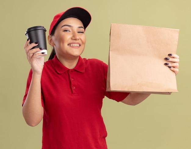 Szczęśliwa młoda kobieta dostawy w czerwonym mundurze i czapce, trzymając pakiet papieru i filiżankę kawy patrząc z przodu z uśmiechem na twarzy stojącej nad zieloną ścianą