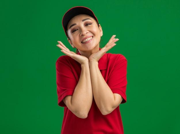 Szczęśliwa młoda kobieta dostawy w czerwonym mundurze i czapce uśmiechnięta przyjaźnie z ręką w pobliżu twarzy stojącej nad zieloną ścianą