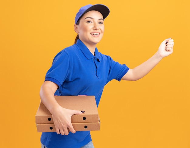 Szczęśliwa młoda kobieta dostawy w niebieskim mundurze i czapce pędzi do dostarczania pudełek po pizzy dla klienta na pomarańczowej ścianie