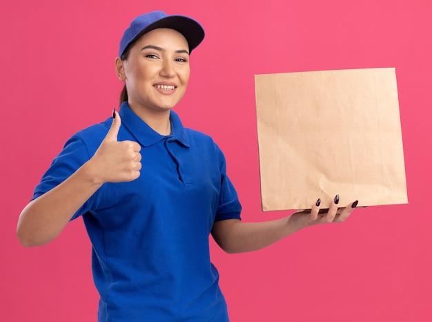 Szczęśliwa młoda kobieta dostawy w niebieskim mundurze i czapce, trzymając papierowy pakiet patrząc na przód, uśmiechając się radośnie pokazując kciuki do góry stojąc nad różową ścianą