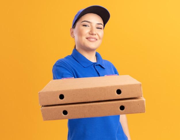 Szczęśliwa młoda kobieta dostawy w niebieskim mundurze i czapce, trzymając pudełka po pizzy, patrząc na przód, uśmiechając się pewnie stojąc nad pomarańczową ścianą
