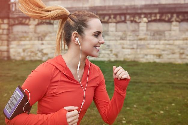 Szczęśliwa młoda kobieta działa na zewnątrz. przygotowuje się do maratonu