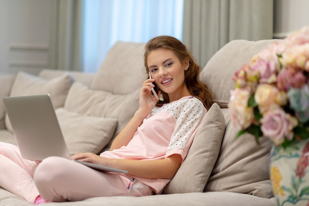 Szczęśliwa młoda kobieta dzwoni mądrze telefonem pracującym na komputerze. atrakcyjna kobieta z telefonem komórkowym i laptopem.