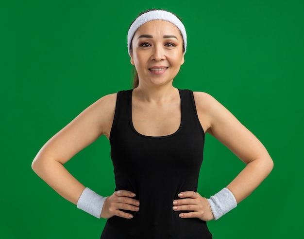 Szczęśliwa młoda kobieta fitness z opaską i opaskami uśmiecha się pewnie stojąc nad zieloną ścianą