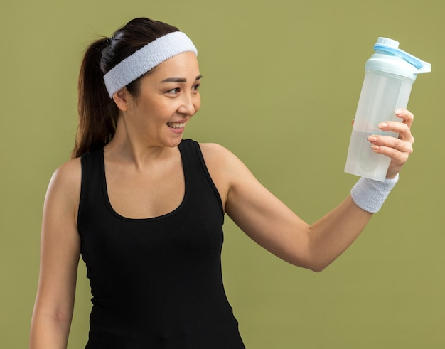 Szczęśliwa młoda kobieta fitness z opaską na głowę trzymająca butelkę wody, patrząc na nią z uśmiechem na twarzy stojącej nad zieloną ścianą