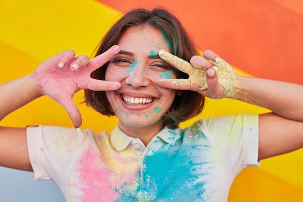 Szczęśliwa młoda kobieta gestykuluje znak v podczas festiwalu farby