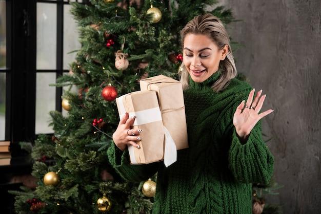 Szczęśliwa młoda kobieta gospodarstwa prezentów bożonarodzeniowych pudełka