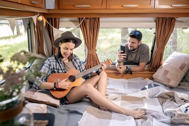 Szczęśliwa młoda kobieta gra na gitarze, podczas gdy jej mąż robi zdjęcie lub wideo