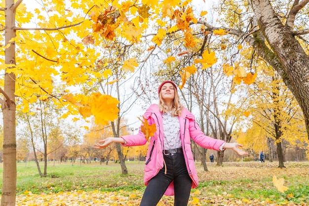 Szczęśliwa młoda kobieta gra pod spadającymi żółtymi liśćmi w pięknym jesiennym parku na spacery na świeżym powietrzu. nastolatka rzuca się jesienią pomarańczowe liście klonu.