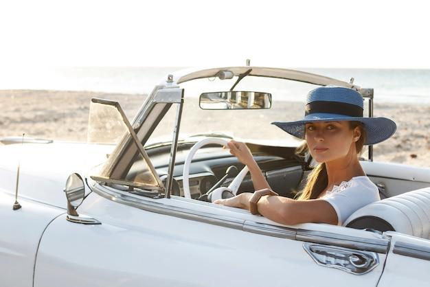 Szczęśliwa młoda kobieta i retro kabriolet przy plaży w mieście varadero