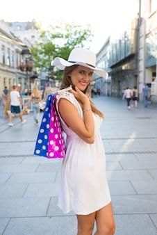 Szczęśliwa młoda kobieta i torba na zakupy na miasto ulicie