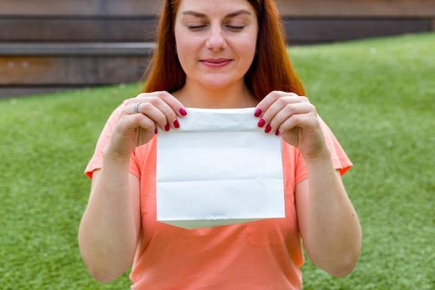 Szczęśliwa młoda kobieta imbir patrząc białą papierową torbę w jej ręce. kobieta trzyma pakiet z jedzeniem. skopiuj miejsce. makieta pustego opakowania
