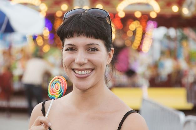 Szczęśliwa młoda kobieta je lollipop