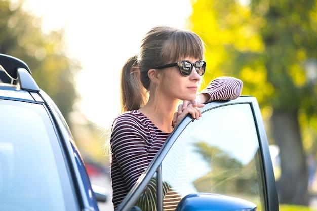 Szczęśliwa młoda kobieta kierowca ciesząc się ciepły letni dzień stojąc obok swojego samochodu na ulicy miasta