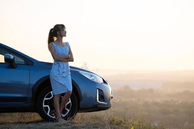 Szczęśliwa młoda kobieta kierowca w niebieskiej sukience, ciesząc się ciepłym letnim wieczorem stojąc obok jej samochodu. koncepcja podróży i wakacji.