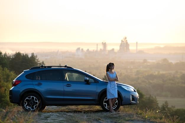 Szczęśliwa młoda kobieta kierowca w niebieskiej sukience, opierając się na swoim samochodzie, ciesząc się ciepły letni dzień.