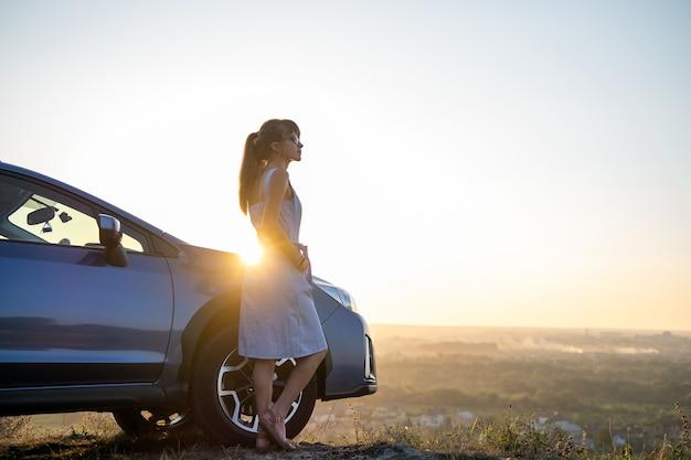 Szczęśliwa młoda kobieta kierowca w niebieskiej sukience, opierając się na swoim samochodzie, ciesząc się ciepłym letnim dniem.