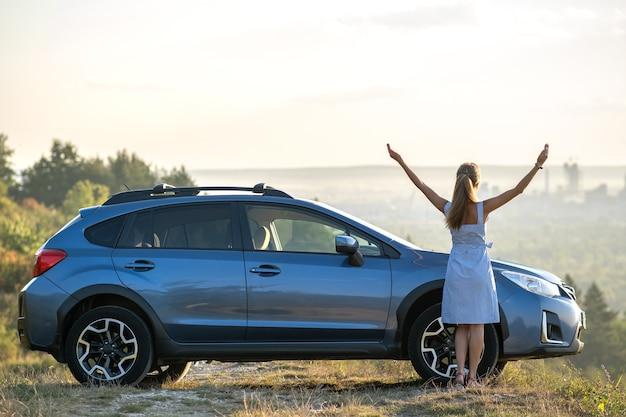 Szczęśliwa młoda kobieta kierowca z wyciągniętymi rękami, ciesząc się ciepłym latem
