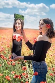 Szczęśliwa młoda kobieta korzystających z wolności w przyrodzie, pole maku. czas letni