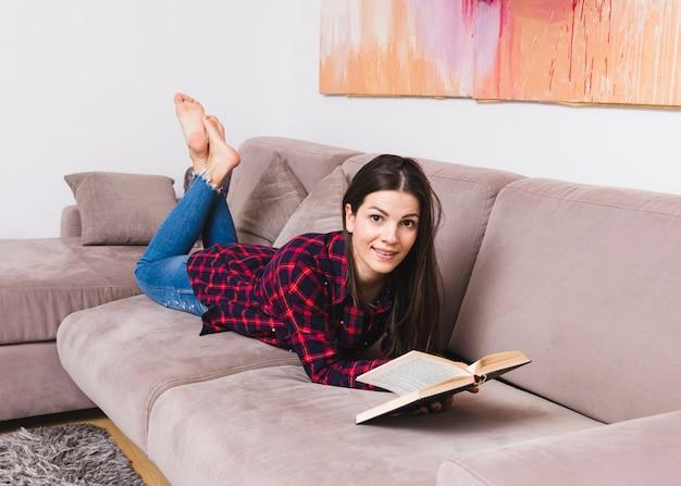 Szczęśliwa młoda kobieta leży na kanapie czytanie książki