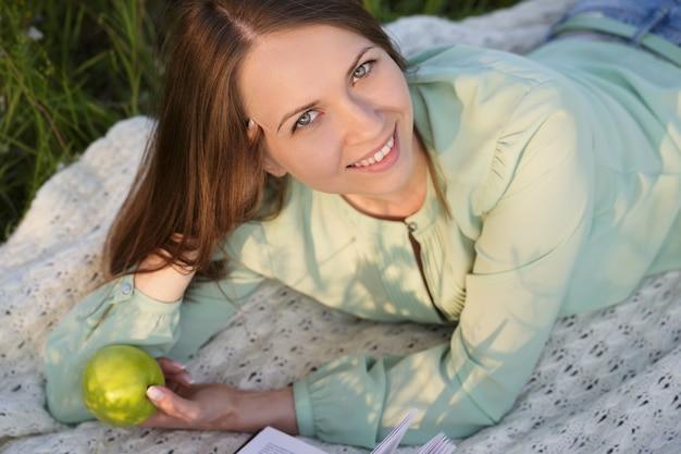 Szczęśliwa młoda kobieta leży na trawie w parku
