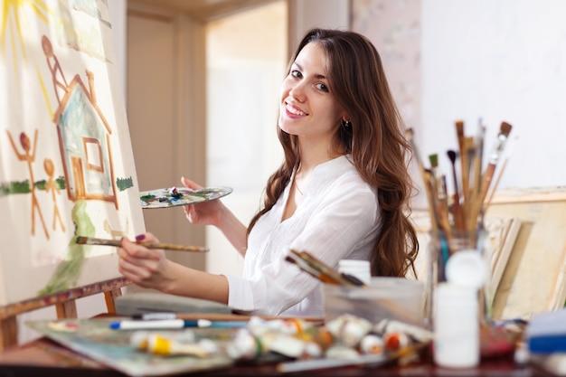 Szczęśliwa młoda kobieta maluje na kanwie