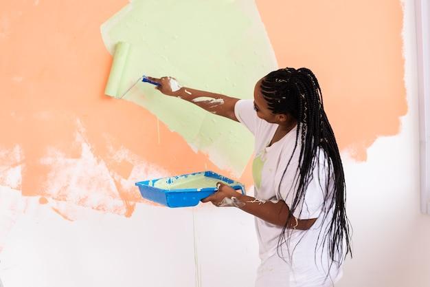 Szczęśliwa młoda kobieta maluje ścianę farbą