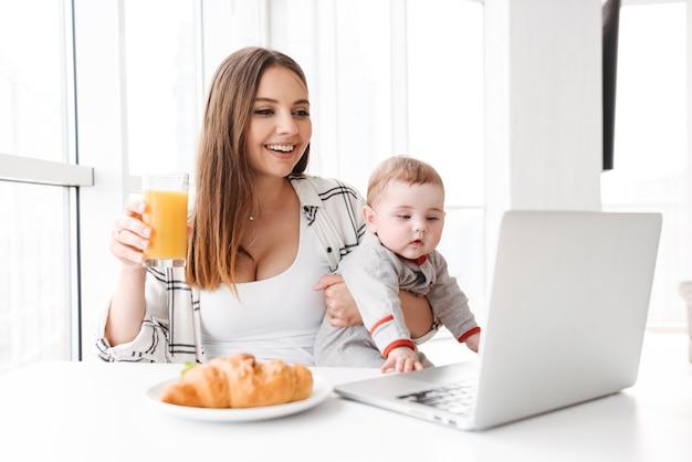 Szczęśliwa młoda kobieta matka za pomocą laptopa z jej małym dzieckiem