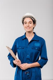 Szczęśliwa młoda kobieta mechanik w niebieskiej odzieży roboczej i kasku ochronnym, trzymając schowek z dokumentem, stojąc w izolacji