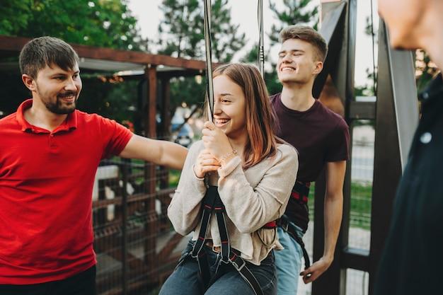 Szczęśliwa młoda kobieta mężczyzna w szelki bezpieczeństwa wiszące i przygotowuje się do jazdy na linie zip z mężczyznami personelu wokół
