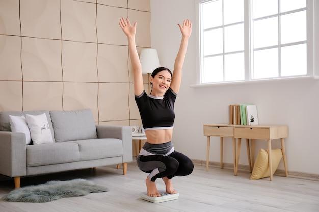 Szczęśliwa młoda kobieta mierzy swoją wagę w domu