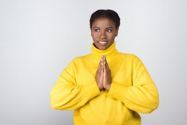 Szczęśliwa młoda kobieta modli się i patrzeje na boku