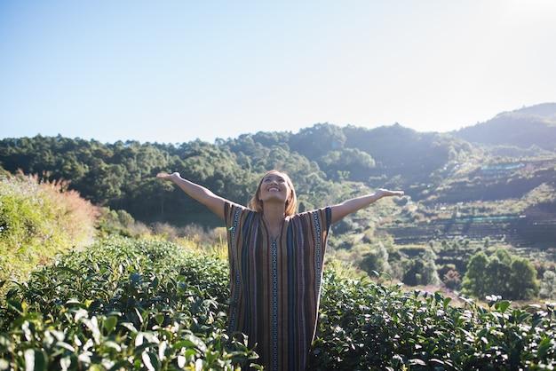 Szczęśliwa młoda kobieta na plantacji herbaty
