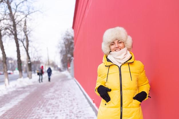 Szczęśliwa młoda kobieta na tle czerwonej ściany w ciepłe ubrania w zimowy słoneczny dzień