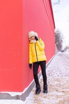 Szczęśliwa młoda kobieta na tle czerwonej ściany w ciepłych ubraniach w zimowy słoneczny dzień uśmiechnięta i rozmawiająca przez telefon na zaśnieżonym chodniku miasta