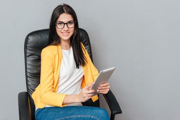 Szczęśliwa młoda kobieta nosi okulary i ubrana w żółtą kurtkę, siedząc na krześle biurowym podczas korzystania z komputera typu tablet na szarej powierzchni.