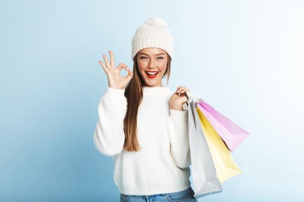 Szczęśliwa młoda kobieta nosi sweter, niosąc torby na zakupy, pokazując gest ok