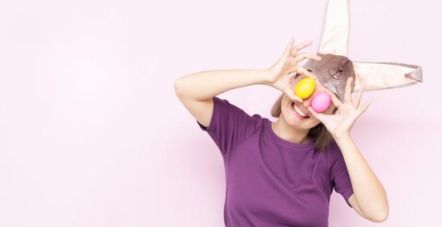 Szczęśliwa młoda kobieta nosi uszy królika i trzyma kolorowe pisanki przed oczami