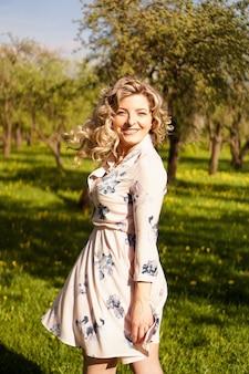 Szczęśliwa młoda kobieta o blond włosach, ubrana w sukienkę, pozowanie na świeżym powietrzu w ogrodzie z wiśniami w słońcu, uśmiechając się. loki trzepoczące na wietrze